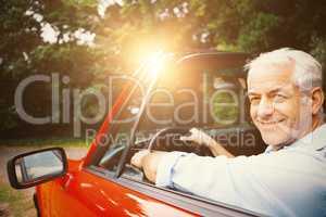 Smiling man driving red car
