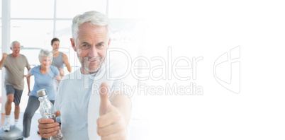 Man showing thumbs up sign with people exercising in background