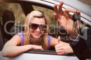 Composite image of happy seller holding car keys