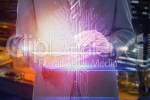Composite image of businessman using digital tablet