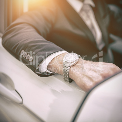 Arm of a man leaning on a car