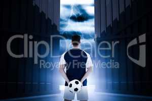 Composite image of rear view of sportsman holding football at his back 3d