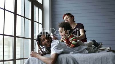 Happy mixed family playing with son in the bedroom