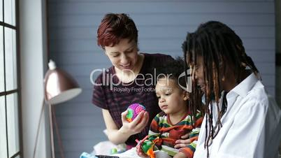 Lovely mixed race toddler having fun with parents