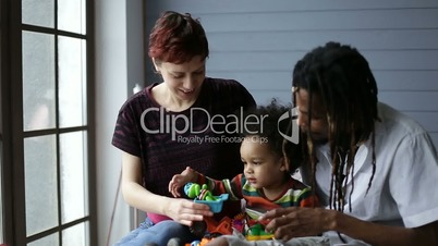 Smiling mixed race family playing with toys