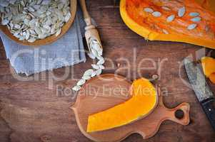 Piece of fresh pumpkin and pumpkin seeds on a brown table