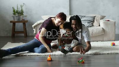 Happy parents playing with toddler son on floor