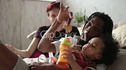 Cute little boy drinking juice from feeding bottle