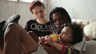 Multiracial curly boy drinking from feeding bottle