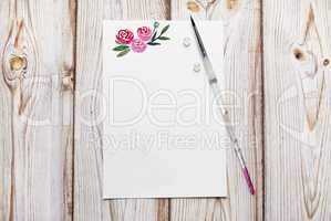 Blank paper with painted roses with the place for your text on a wooden background.
