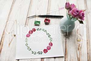 Artist workspace with watercolor, brush, bouquet of roses, hand drawn floral wreath frame on a wooden background.