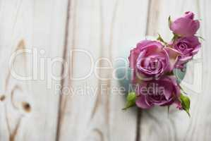 Vase with a bouquet of pink roses on a wooden background with the place for your text.