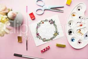 Artist workspace. Floral wreath frame hand painted with watercolor, bouquet of chrysanthemum and roses, glasses, paintbrush, scissors, watercolor, palette on a pink background.