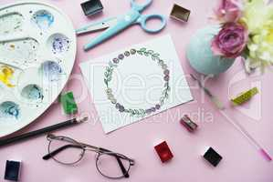 Artist's workspace. Floral wreath frame painted with watercolor, vase with a bouquet of flowers, glasses, paintbrush, scissors,