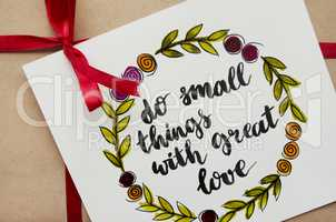 Inspirational quote do small things with great love written in calligraphy style. Gift in kraft paper with a red ribbon. Flat lay