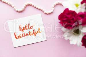 Inspirational quote Hello beautiful written in calligraphy style with watercolor. Composition on a pink background. Flat lay