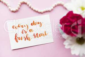 Inspirational quote Every day is a fresh start written in calligraphy style with watercolor. Composition on a pink background. Flat lay