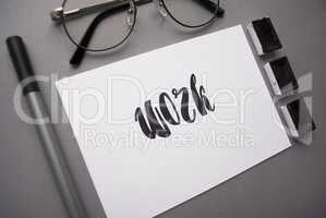 Composition with word work written in calligraphy style, liner, black watercolor, glasses on gray background. Top view