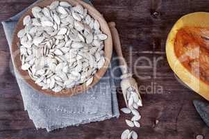 Pumpkin seeds in a wooden bowl with a piece of fresh pumpkin