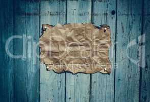 Brown rumpled kraft paper hanging on a blue wooden surface