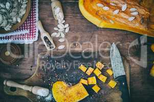 Pieces of pumpkin in salt and pepper on a kitchen cutting board