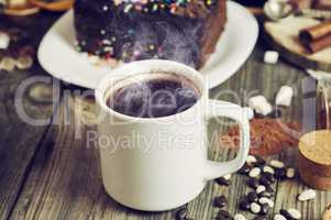 White cup with hot black coffee on a gray wooden surface