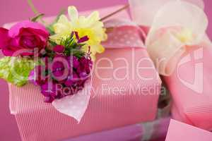 Gift boxes with flowers and blank card against pink background