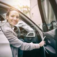 Woman sitting in a car and smiling at camera