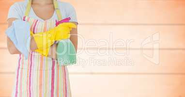 Woman in apron with arms folded and cleaner against blurry orange wood panel