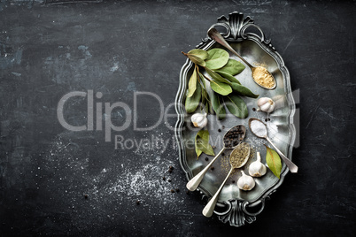 Dark culinary background with bay leaves, salt, pepper and garlic