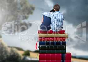 Couple sitting on Books stacked by romantic nature landscape