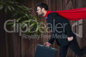 Confident business man super hero walking against wooden background with leaves