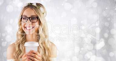 Woman with flowers in hair and white coffee cup against white bokeh