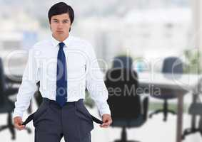 Sad businessman with empty pockets against office background