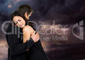 Sad couple hugging against dark cloudy sky