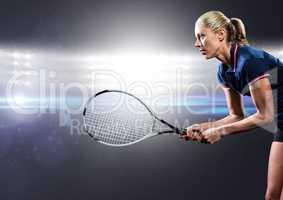 Tennis player with racket outstretched against bright lights