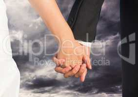 Wedding couple holding hands by bed