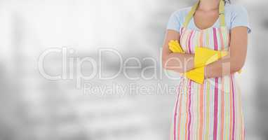 Woman in apron arms folded against blurry grey background