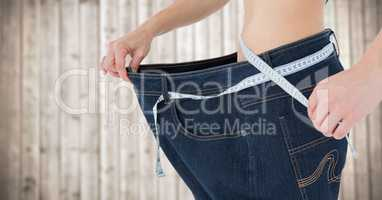 Woman with large pants and measuring tape against blurry wood panel