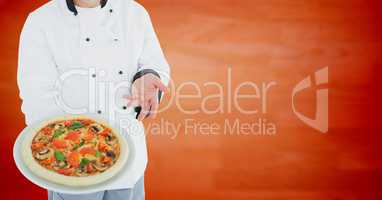 Chef with pizza against blurry orange wood panel