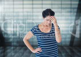 Stressed woman against windows