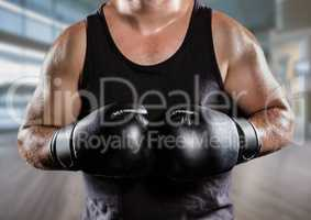 Man with boxing gloves mid sections against blurry gym