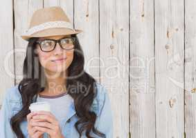 Woman with fedora and white coffee cup against white wood panel
