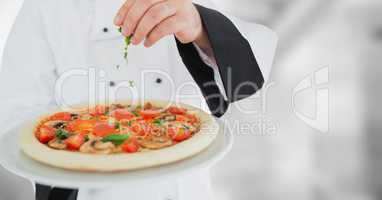 Chef putting herbs on pizza against blurry grey background