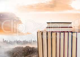 Books stacked by distant city and clouds