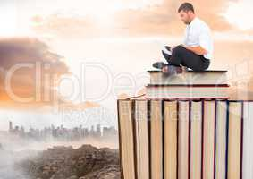 Man with laptop sitting on Books stacked by distant city and clouds