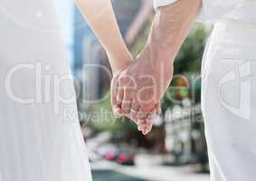 Wedding couple holding hands in city