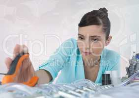 Woman with electronics and pliers against white background with interface