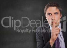 Business man finger over mouth against concrete wall