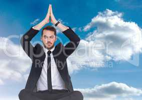 Businessman Meditating by clouds